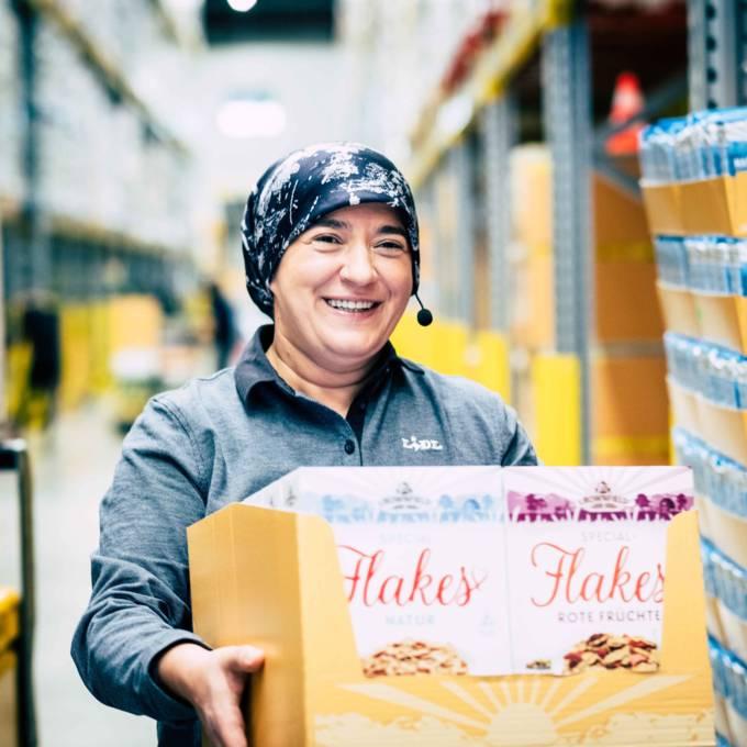 Lidl Mitarbeiterin Aishe trägt einen Karton
