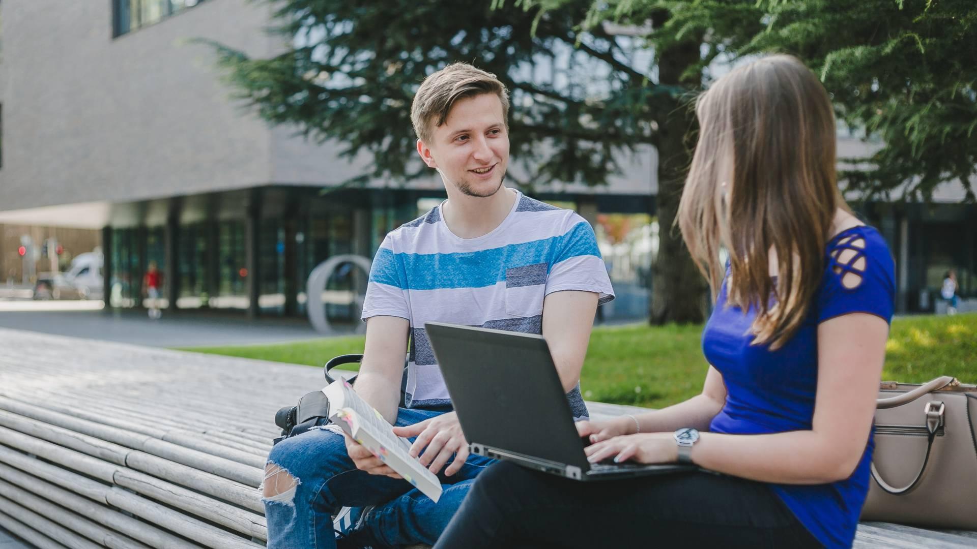 Studenten im Gespräch auf einer Bank