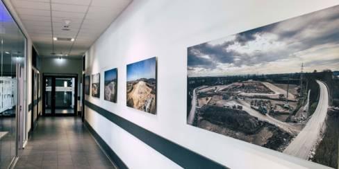 Bilder von Baumaßnahmen neuer Lidl-Filialen als Dekostücke in der Zentrale.